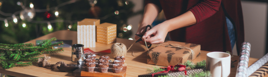 Woman in Burgundy shirt using scissors to wrap gifts for Christmas