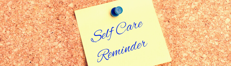 Self Care reminder written in blue ink on yellow sticky note